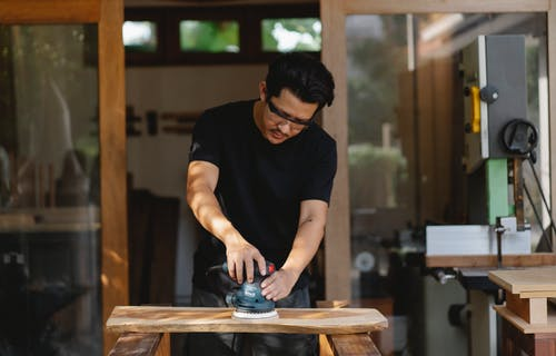 Concentrated male master in protective glasses smoothing wooden plank with sander while creating wooden detail in workroom