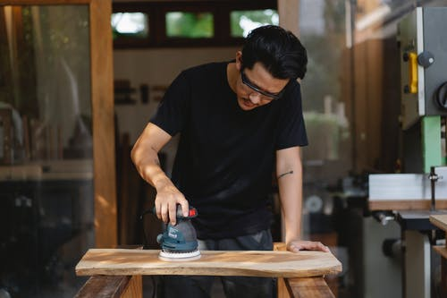 Joiner polishing wooden board with carpentry instrument
