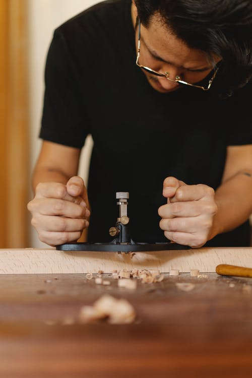 Crop concentrated male master in glasses processing wood with manual router plane in joinery workshop