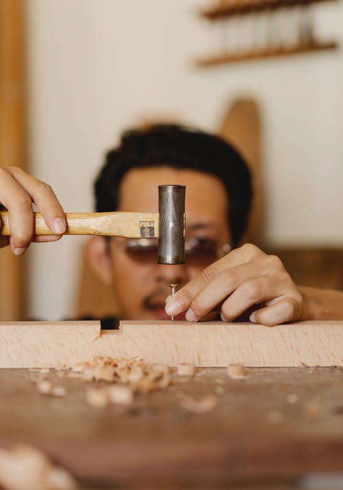 Carpenter hammering nail in workshop