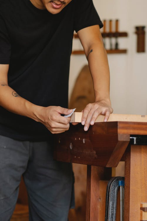 Unrecognizable craftsman in casual clothes polishing wooden detail while working in professional workshop