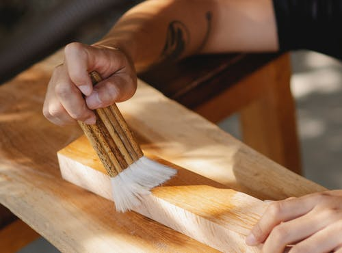 Craftsman varnishing wooden plank in workshop