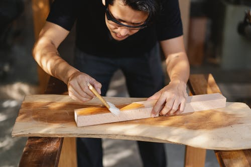 Young ethnic carpenter applying protective varnish on wooden detail while working in professional workshop