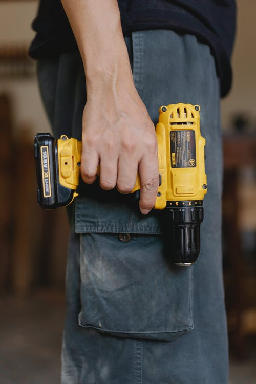 Side view of unrecognizable craftsman in casual clothes standing with electric cordless screwdriver in workshop