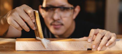 Professional artisan varnishing wooden detail in workplace