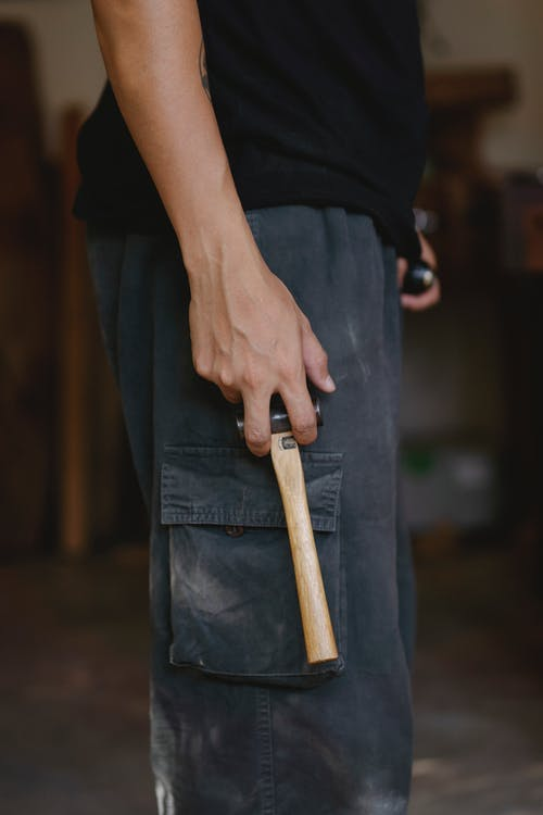 Side view of unrecognizable craftsman in casual clothes standing with hammer in workshop