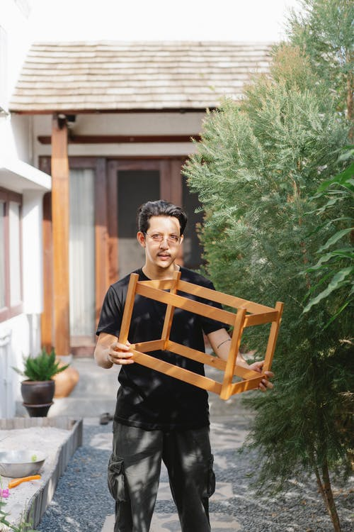 Young Asian craftsman in casual clothes carrying wooden construction in garden and looking at camera