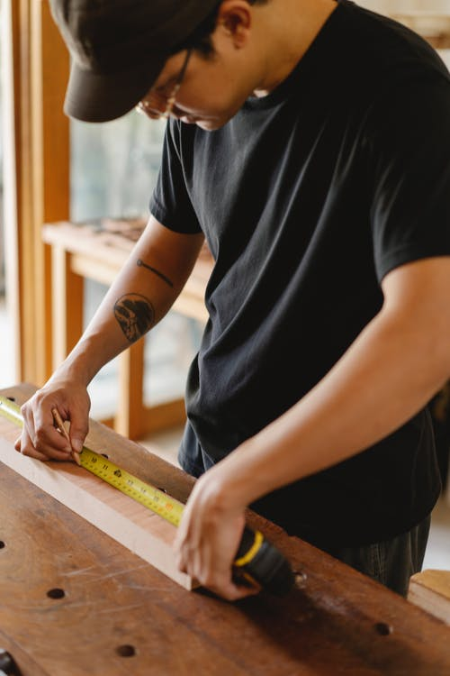High angle of crop craftsman in cap and eyeglasses making sign measuring wooden plank with tape measure while working in workshop