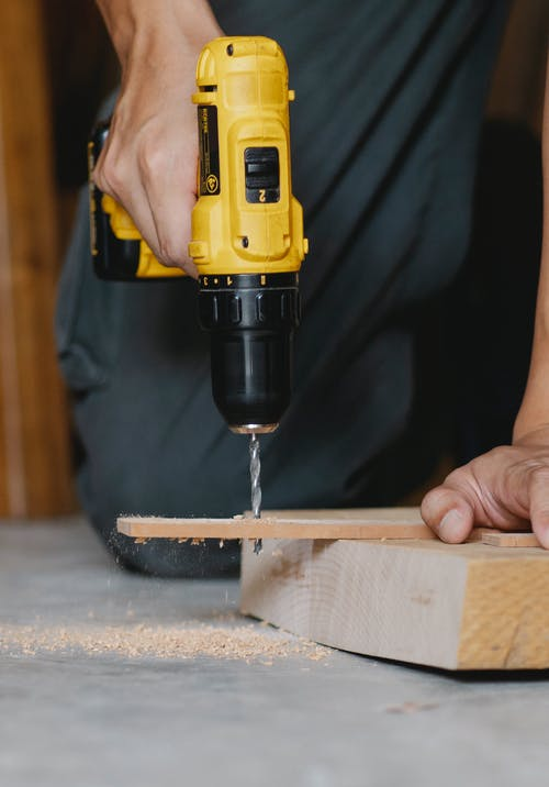 Crop unrecognizable carpenter in black outfit using modern yellow screwdriver to drill hole in wooden blank while working in joinery