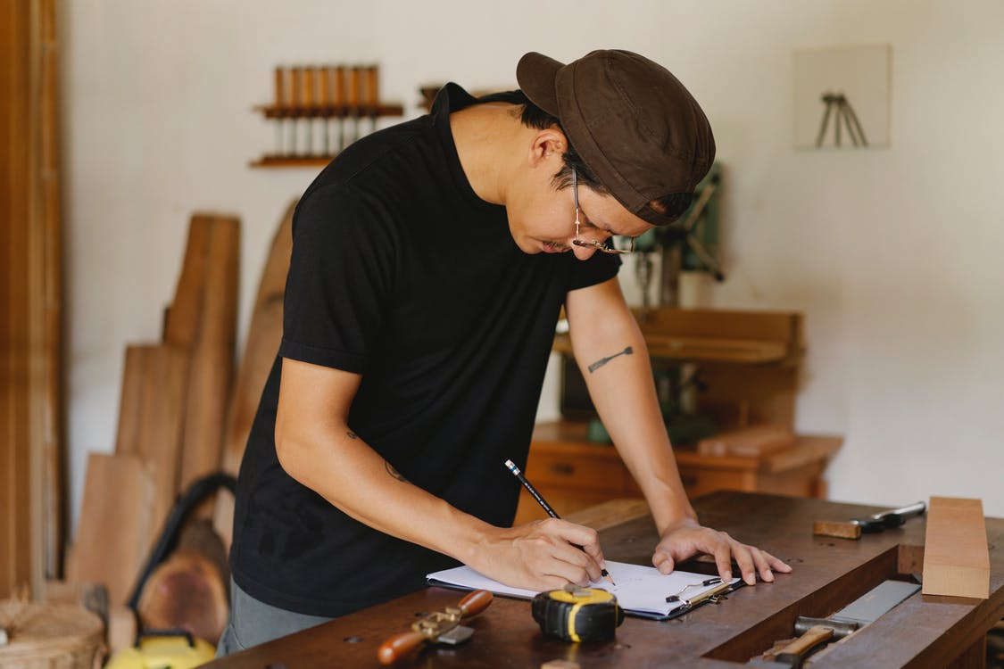 Side view of Asian man in casual clothes and eyeglasses bending on table and taking notes by pencil while working in joinery