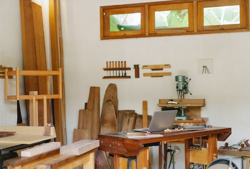 Laptop placed on table in woodworker workshop