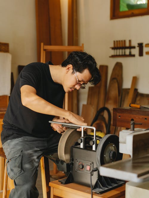 Side view of focused young ethnic male carpenter in casual clothes and eyeglasses using pedestal grinder while creating wooden object in workshop