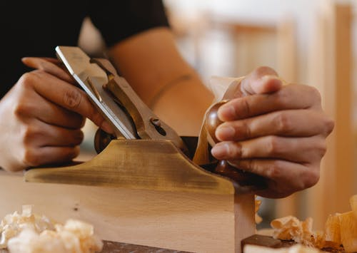 Faceless man flattening lumber board with hand plane in joinery
