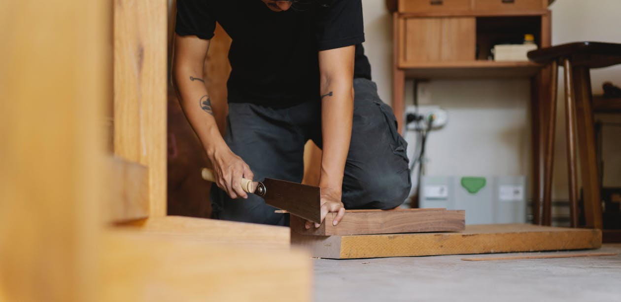 Crop anonymous male carpenter in casual clothes using flush cut saw while creating wooden object in workshop in daylight