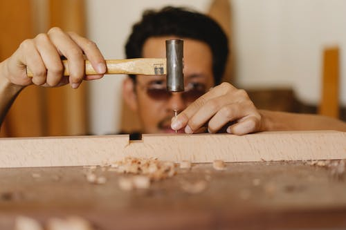Focused ethnic male carpenter hammering nail into wooden detail in workshop