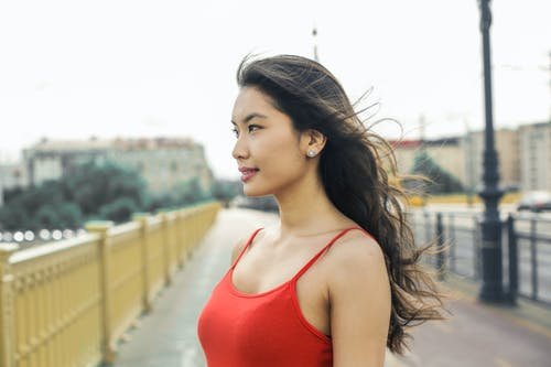 Woman in Red Tank Top Standing on Road