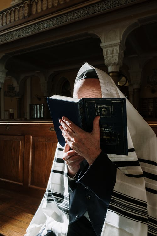 Woman in White Hijab Holding Blue Book