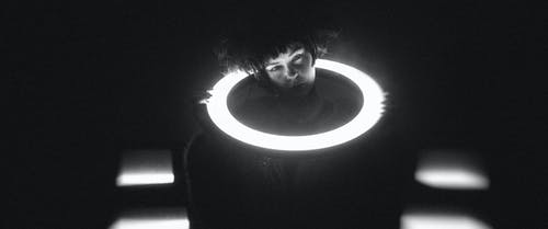 Grayscale Photo of Girl in Round Hole