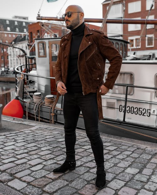 Man in Brown Leather Jacket and Black Pants Standing on Sidewalk