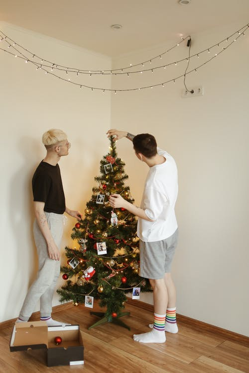 Man in White T-shirt and Black Shorts Standing Beside Christmas Tree