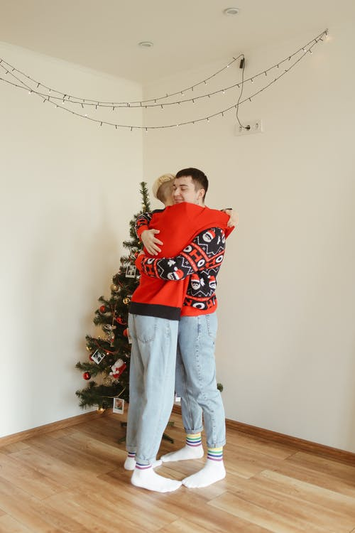 Boy in Red and White Sweater and Gray Pants Standing Beside Green Christmas Tree
