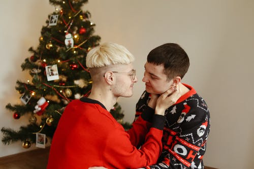 Man in Red Sweater Kissing Woman in Black and White Floral Shirt
