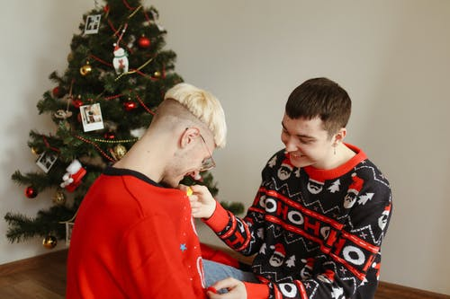 Man in Red Sweater Kissing Woman in White Hair