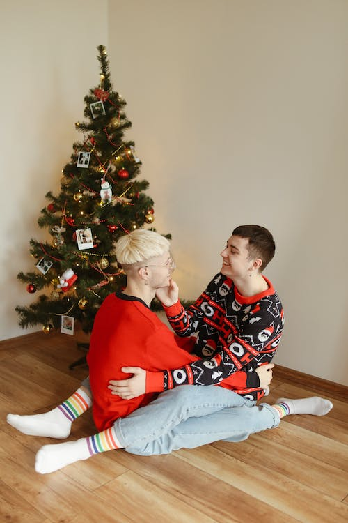 Man and Woman Sitting on Brown Wooden Chair Beside Green Christmas Tree