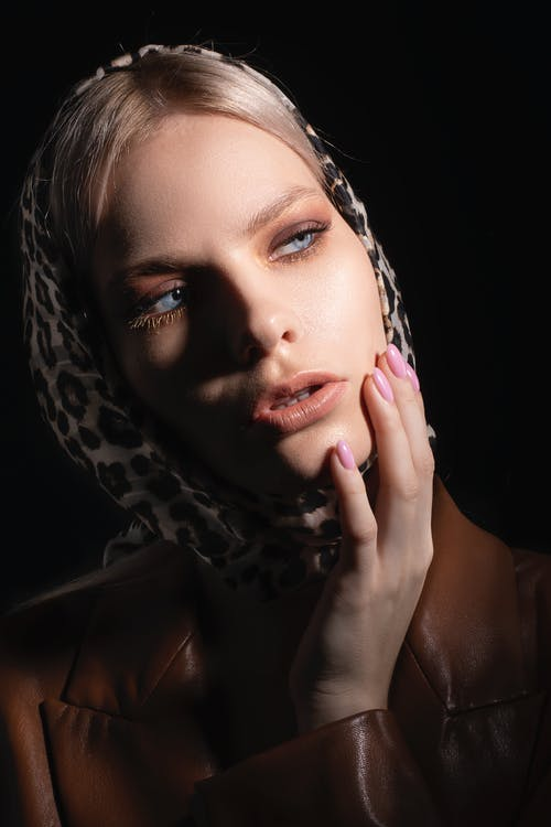 Trendy female in headscarf with leopard print looking away and touching face on black background of studio