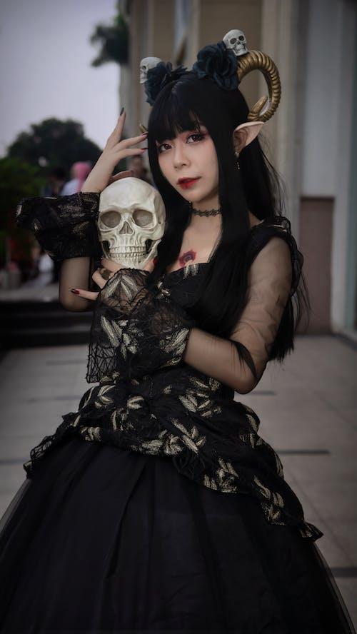 Woman in Black Dress Wearing White Skull Mask