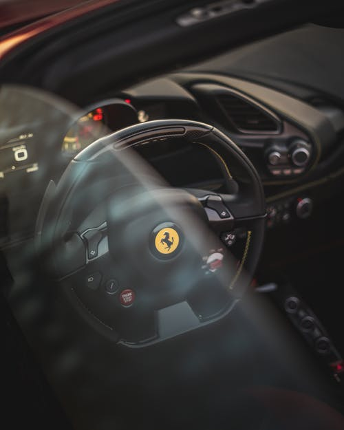 Through window of dashboard of prestige automobile with sport steering wheel and speedometer