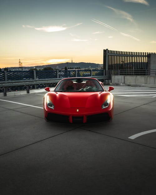 Modern prestige red automobile with bright luminous headlights under cloudy sky in bright sunset