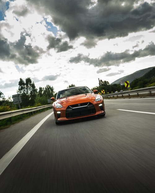 Bright orange expensive car driving fast on asphalt road