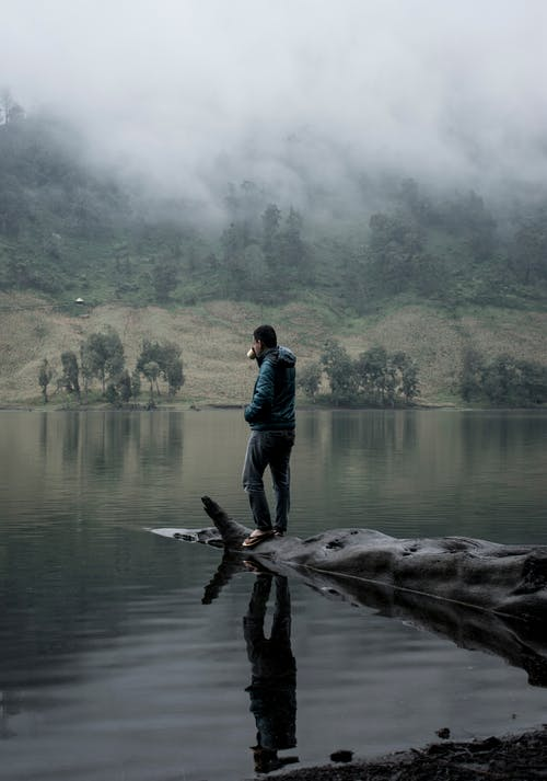 Man standing on tree trunk on water
