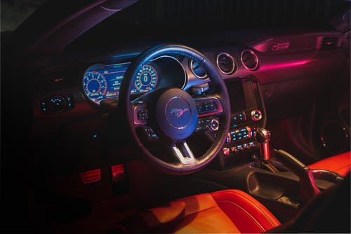 Interior of contemporary car with glowing dashboard and computer behind steering wheel and leather seats