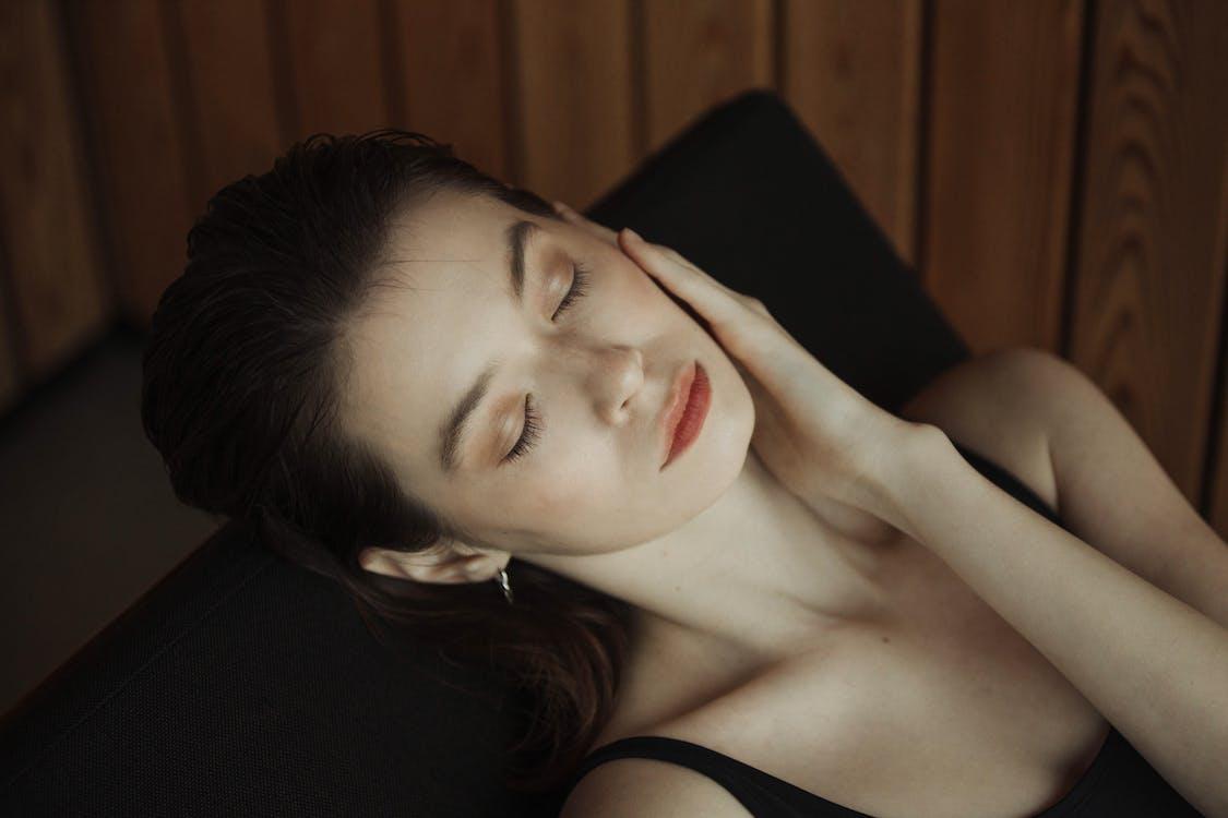 Woman in Black Tank Top Lying on Black Sofa