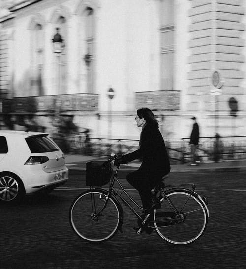 Black and white side view of elegant female in casual outfit and glasses riding vintage bike with basket along road in city