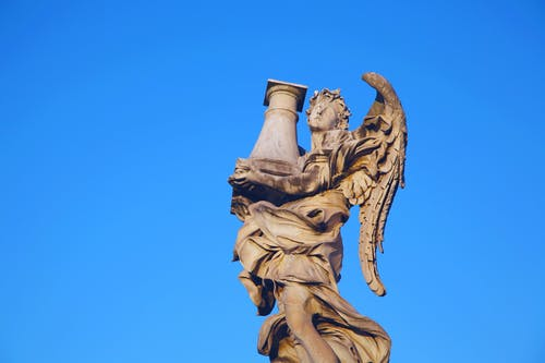 Ancient marble angle sculpture under bright blue sky
