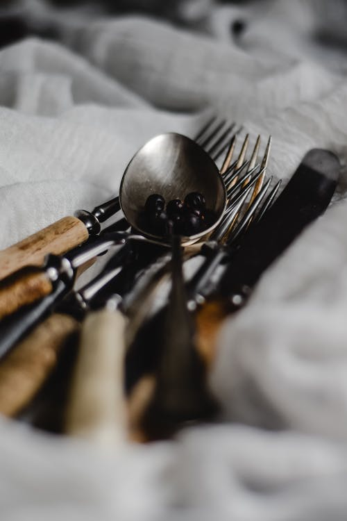 Stainless Steel Spoon and Fork on White Textile