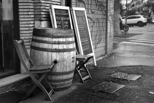 Black and white wooden barrel and chairs placed outside coffee shop near menu chalkboard