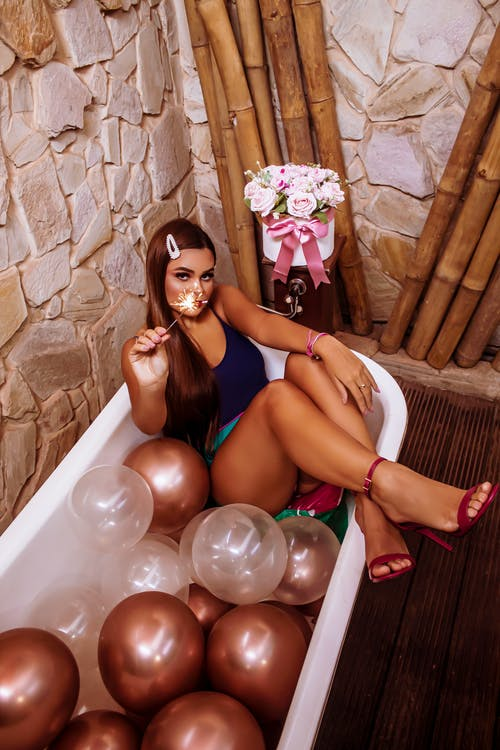 Glamour woman resting in bathtub with balloons on party