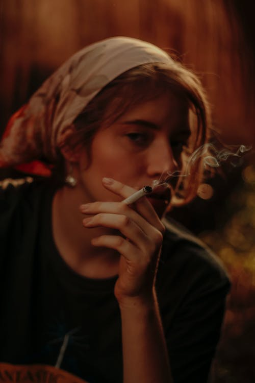 Pensive woman in headscarf smoking cigarette