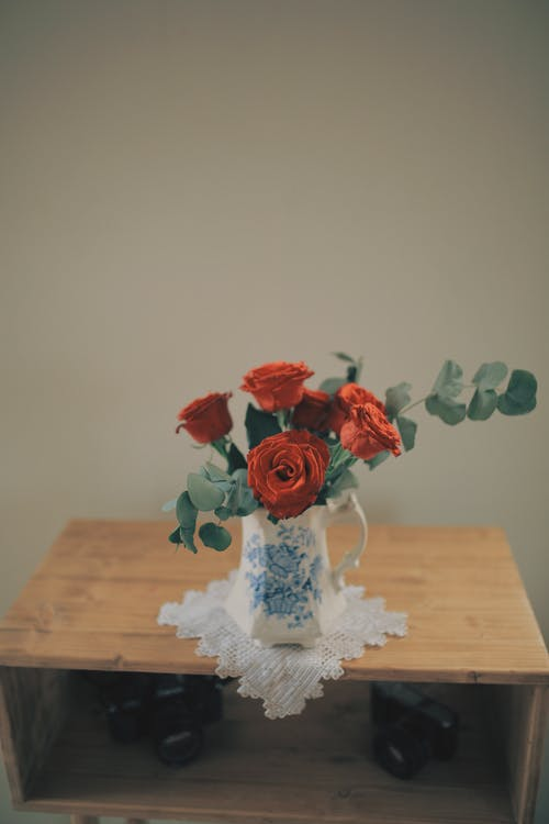 High angle of colorful bouquet of fresh red roses placed in porcelain vase on white knitted napkin located on wooden table with photo cameras below