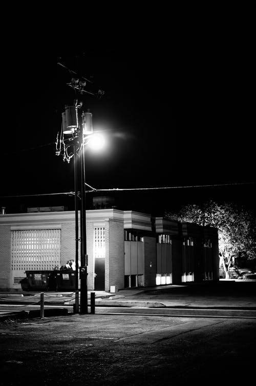 Black and white of small building on empty street with bright luminous streetlamp