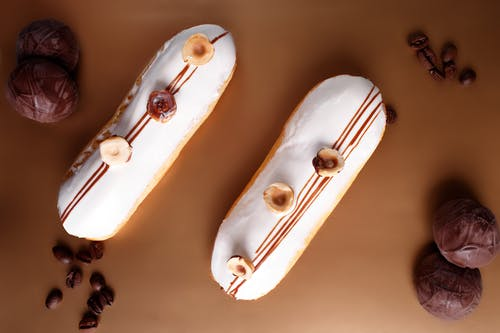 Top view composition of sweet vanilla eclairs topped with hazelnuts and placed on brown table amidst chocolate marshmallow and coffee beans