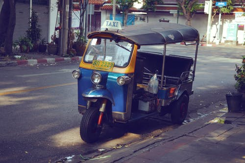 Tuk tuk scooter parked on roadside in rural area