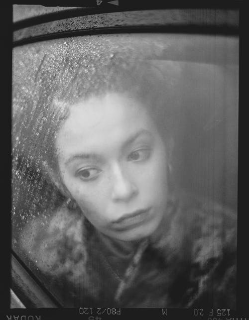 Grayscale Photo of a Lonely Woman Leaning on a Car Window