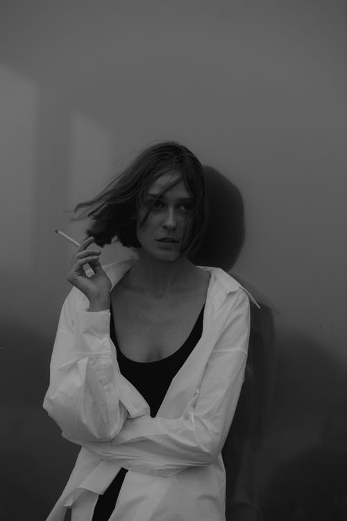 Grayscale Photo of Woman in White Long Sleeve Shirt Smoking a Cigarette