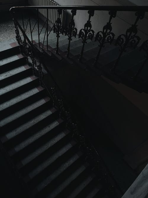 From above of stairway with black metal railings and ornamental elements placed inside old multistory residential house with dim light