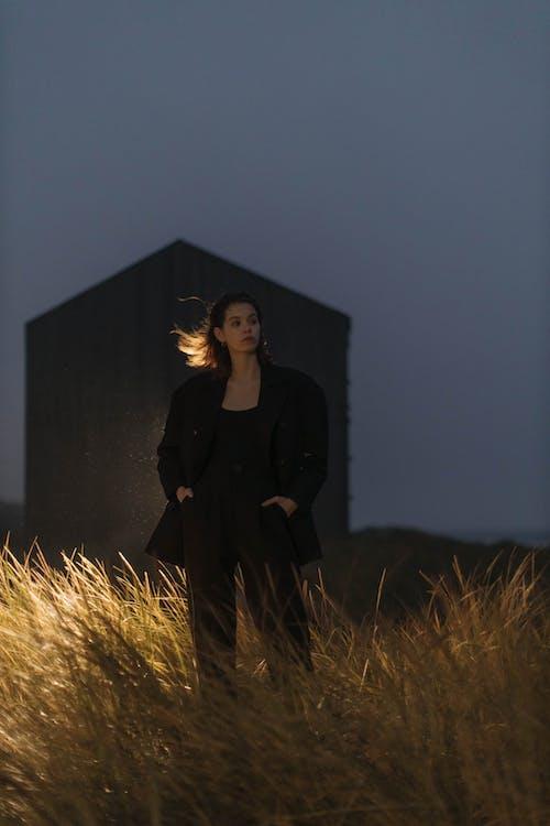 Woman in Black Coat Standing on Brown Grass Field